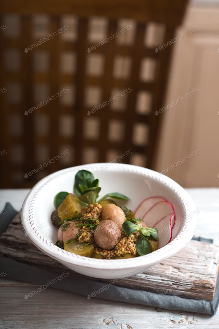 Salad with potatoes, cucumber and radish ceramic bowls side view