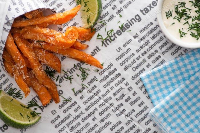 Draufsicht auf knusprige Pommes Frites, Limettenscheiben, Baumwollserviette und Knoblauch-Sauce auf Zeitung