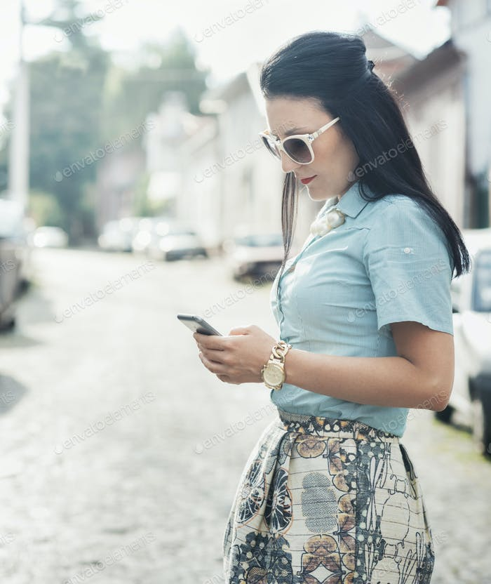 Fashionable woman texting on the street