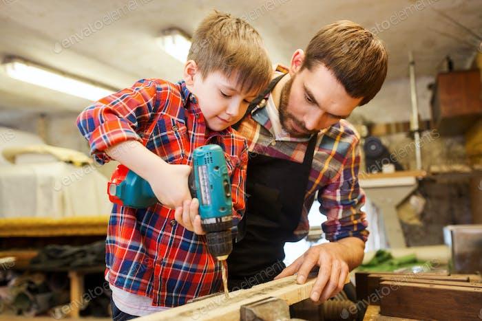 Vater und Sohn mit Bohrer arbeiten in der Werkstatt