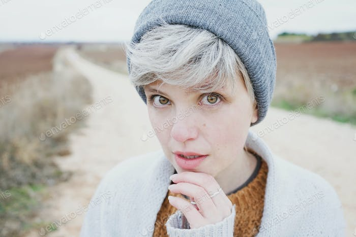 Woman with short and gray hair is alone in the beggining of a ru
