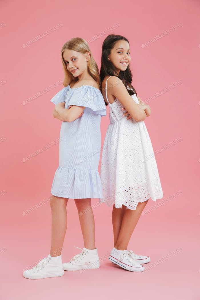 Full length photo of brunette and blonde girls wearing dresses s