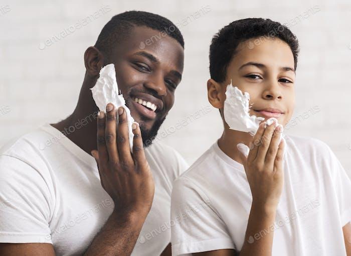 Fröhlicher Afroamerikaner Vater und Sohn Putting Rasierschaum auf Gesichter