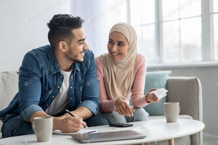 Positive muslim family counting their spendings, feeling wealthy