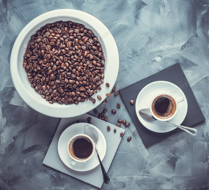 Coffee beans in plate and cup of espresso on abstract painted background texture. Cup of cooffee