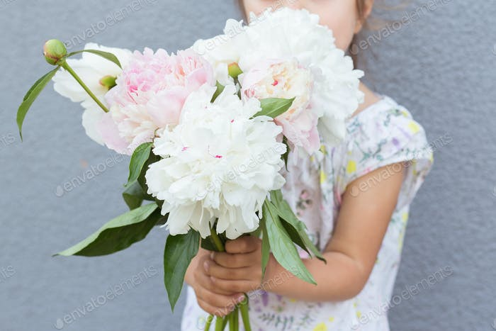 Portrait of a beautiful little girl with a bouquet of peonies