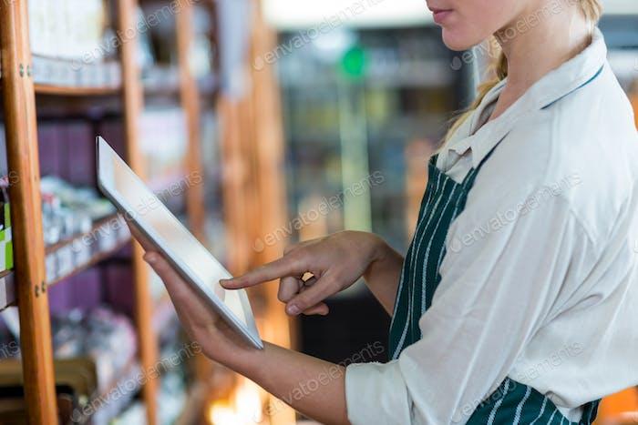 Weibliche Mitarbeiter mit Digital-Tablet im Supermarkt