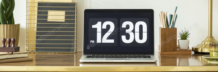 Panorama and close-up on clock on laptop desktop on wooden desk