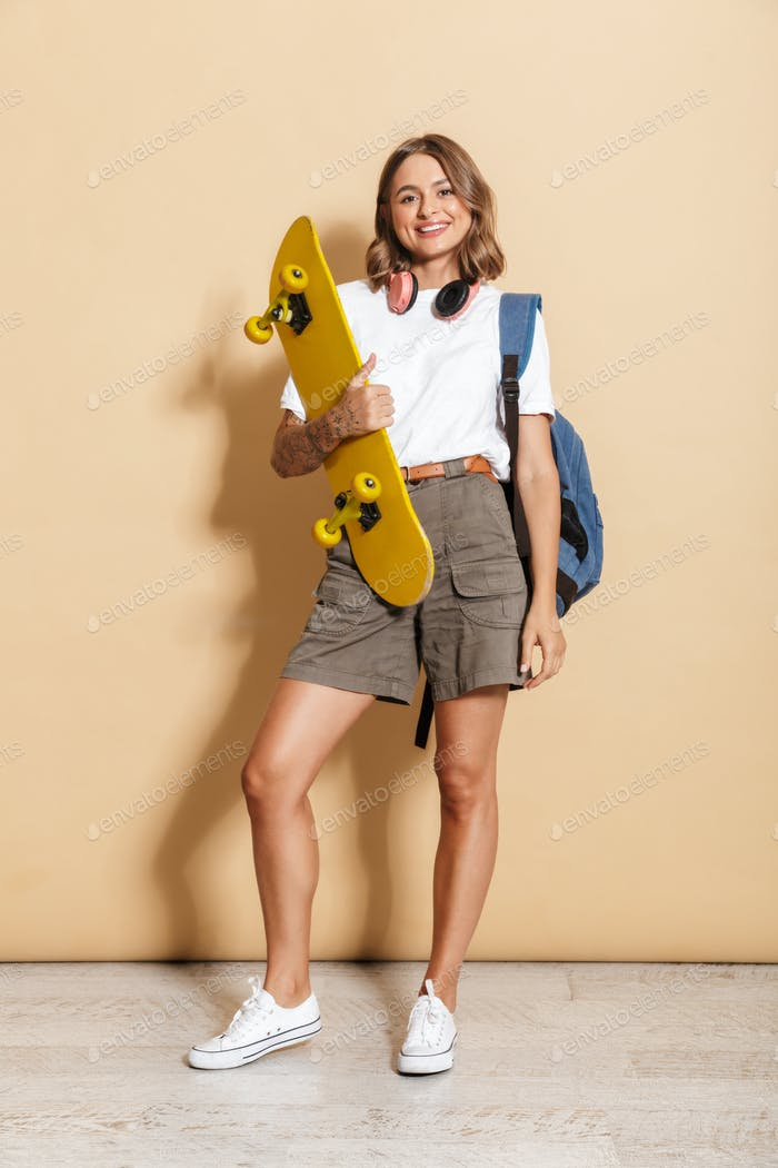 Image of teen girl wearing headphones smiling and holding skateboard