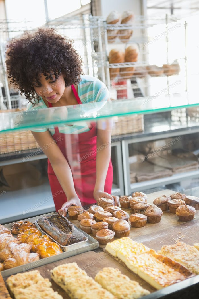 Smiling employee moving over the pastry at the bakery