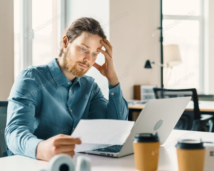 Young businessman looking at financial document or bill with frustrated expression