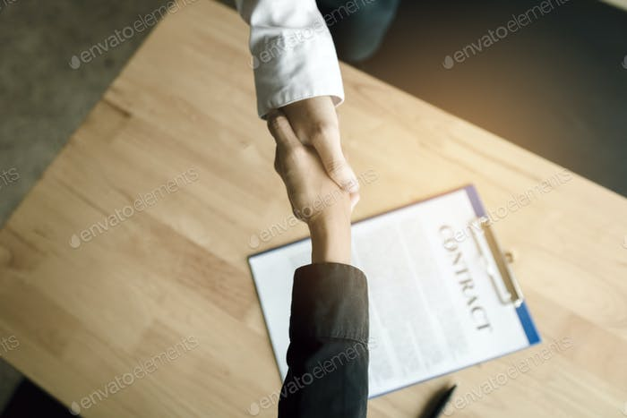 Business people shaking hands with making a contract in the office.