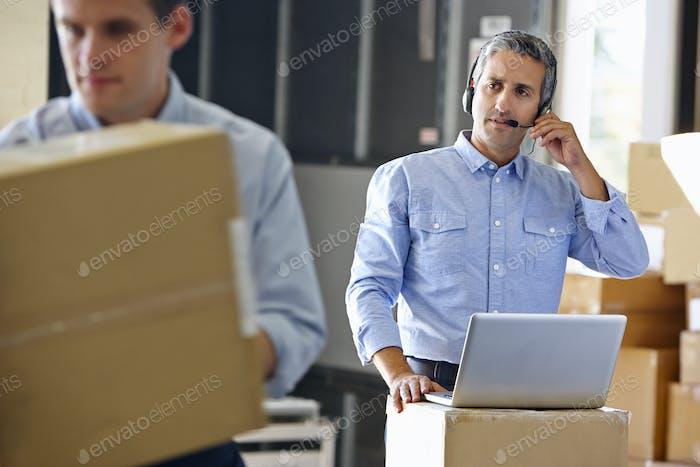 Manager mit Headset im Distributionslager