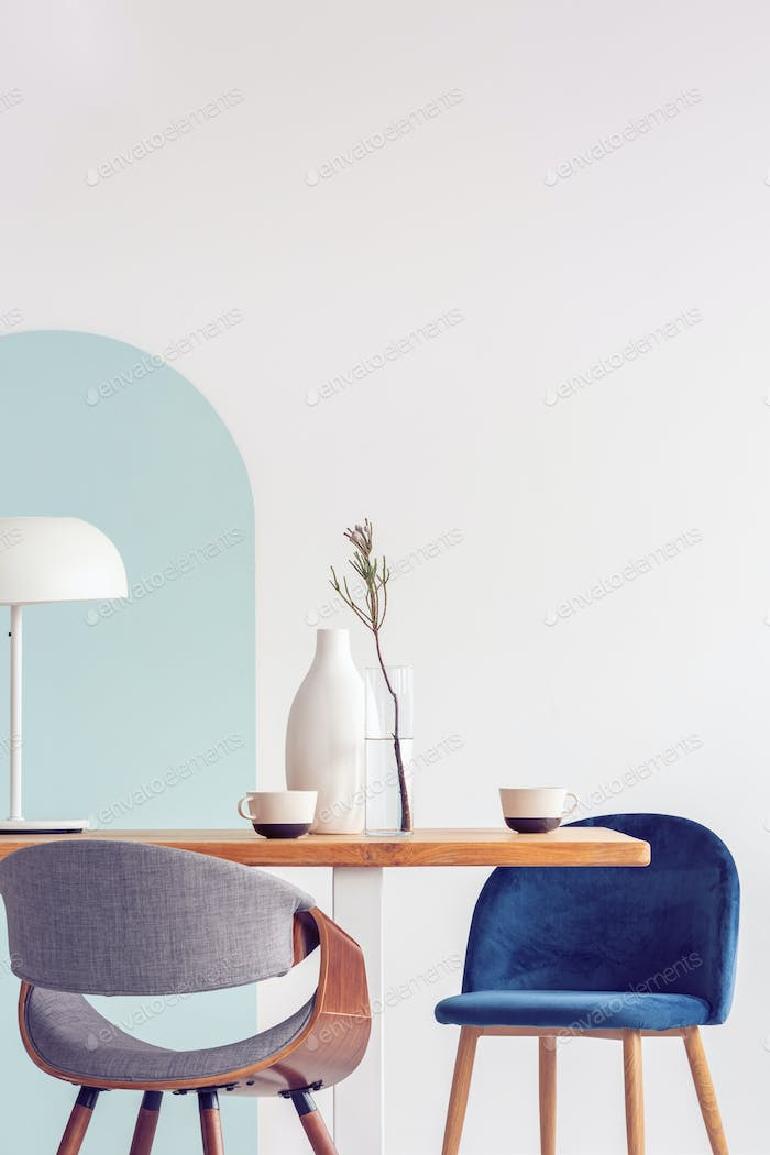Stylish pastel pink and petrol blue chairs at long wooden table in bright dining room