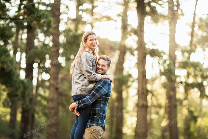 Smiling handsome man holding his girlfriend in the nature