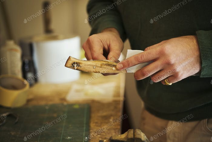 Close up of a craftsman fixing a smooth shaped wooden handle onto a newly made knife blade.