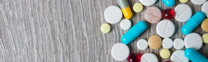 Banner of A lot of colorful medication and pills from above on grey wooden background.