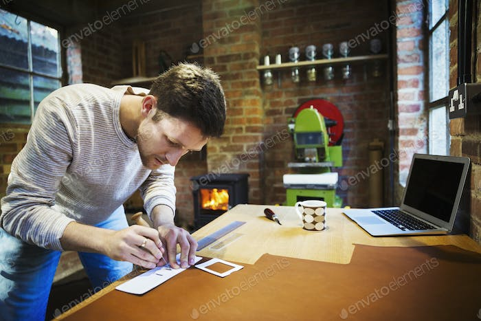 A craftsman using an awl and a ruler to measure and mark a small piece of leather.  Workbench with a