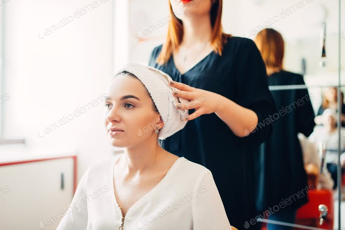 Hairdresser and female client, hair coloring process