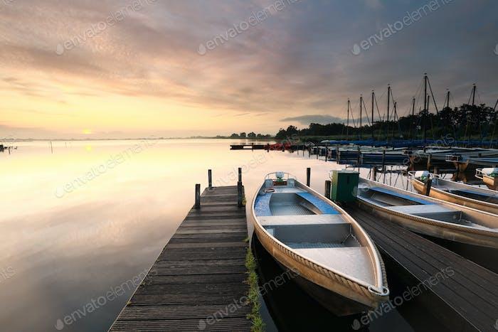 boat at pier on big lake at sunrise