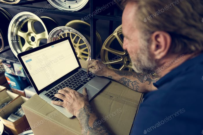 Car Parts Shop Owner Warehouse Checking Emails Concept