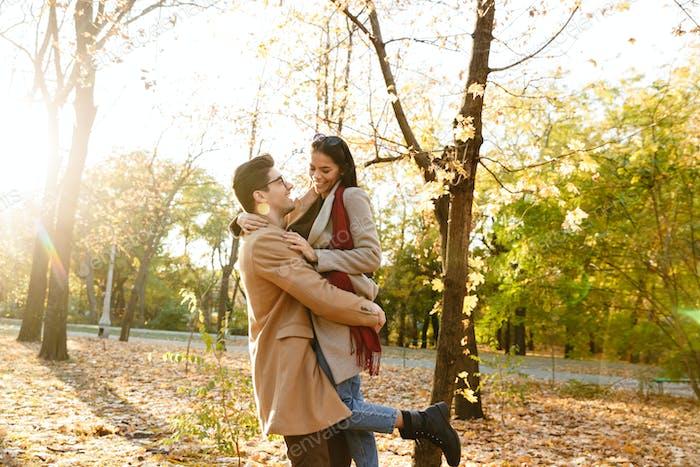 Bild des jungen Mannes trägt Frau in den Händen und lächelnd im Herbstpark