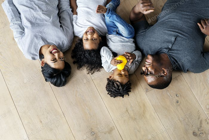 Black family lying on wooden floor design space