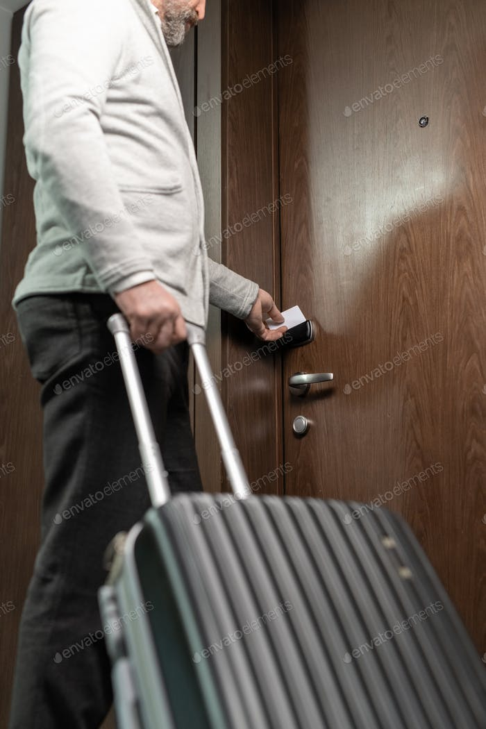 Mature traveler opening door of hotel room