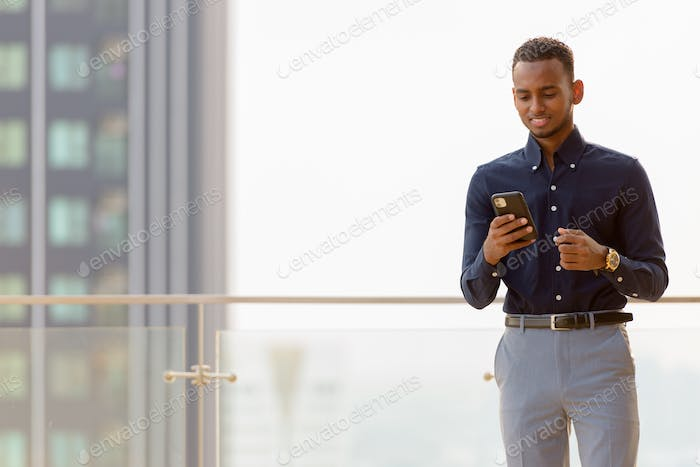 Portrait of handsome African businessman outdoors at rooftop