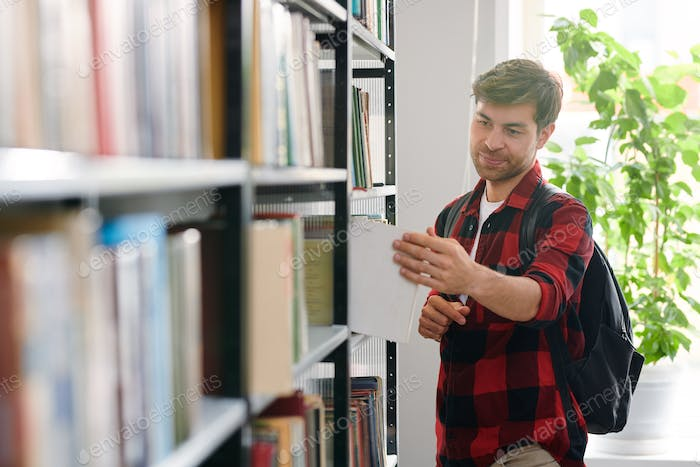 College student with backpack looking through books in college library