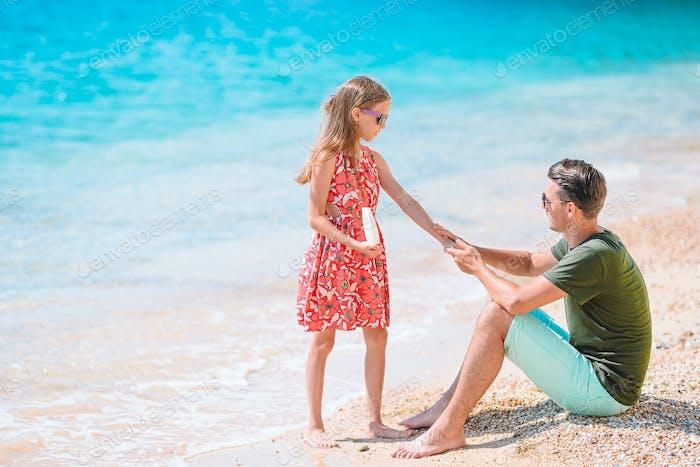 Junger Vater Anwendung Sonnencreme auf Tochter Nase am Strand. Sonnenschutz