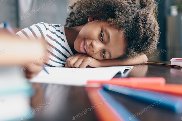 Tired little girl sitting at the table, with her head on her arm, writing in her notebook