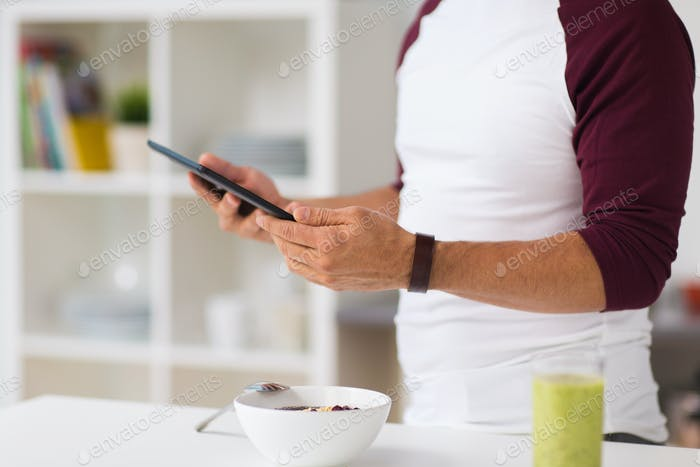 man with tablet pc having breakfast at home
