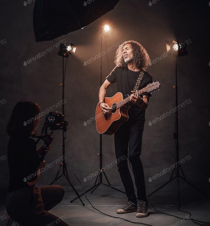 Videofilmer schießt, wie ein talentierter lateinamerikanischer Musiker Gitarre im Studio spielen