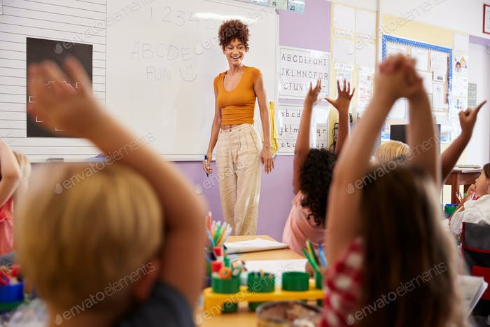Pupils Raising Hands To Answer Question In Elementary School Maths Lesson