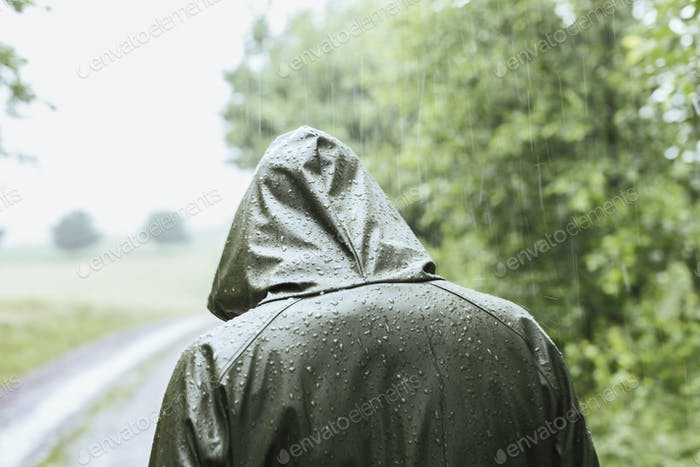Rear view of woman in green raincoat walking in rain
