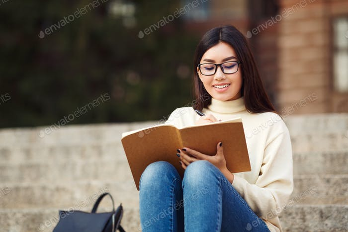 Young girl preparing for lecture in campus