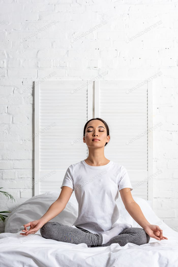 asian woman in white t-shirt and grey leggings sitting in lotus pose in bed