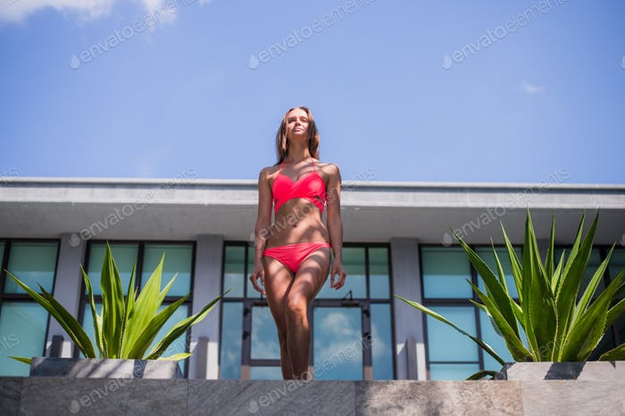 young sexy beautiful woman in pink bikini, posing on terrace of resort hotel, slim, tanned skin