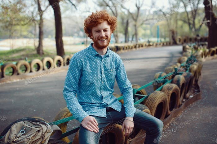 Outdoor portrait of young handsome smiling ginger man