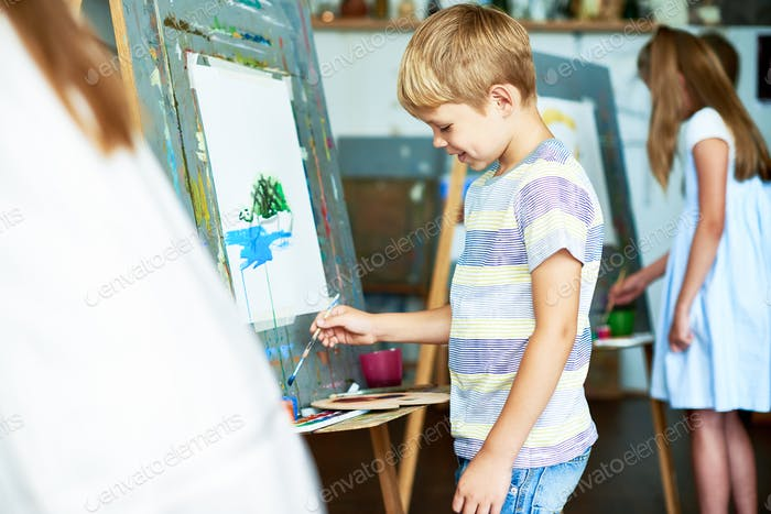Little Boy Painting Picture in School