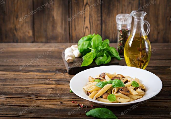 Vegetariano pasta penne con setas en cuenco blanco sobre mesa de De madera. Comida vegana.