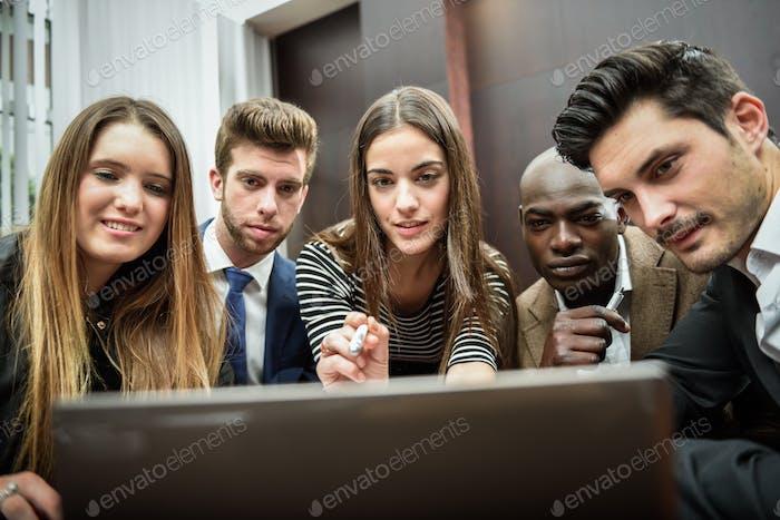 Gruppe von multiethnischen beschäftigten Menschen, die einen Laptop anschaut