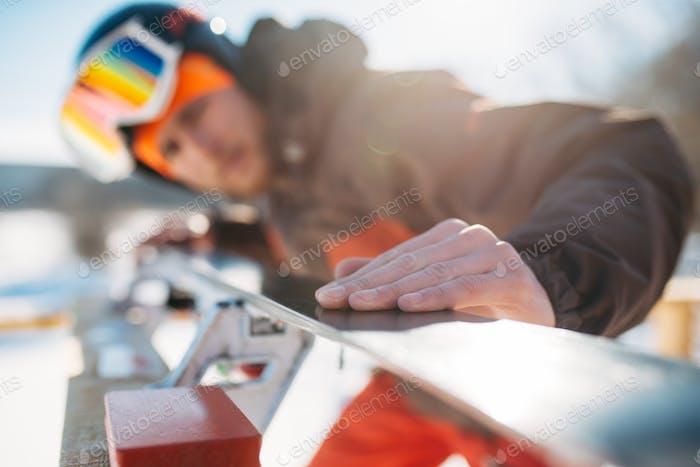 Männlicher Skifahrer überprüft Ski vor dem Skifahren, Wintersport