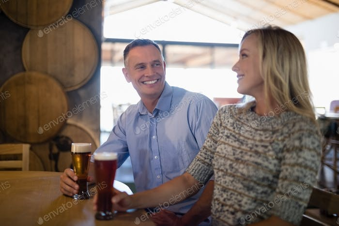 Couple interacting with each other while having beer in bar