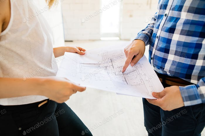 Unrecognizable young couple at the construction site.