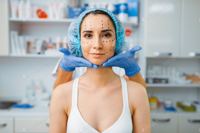 Cosmetician and patient with markers on her face