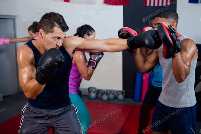 Male boxer and instructor practicing with boxing