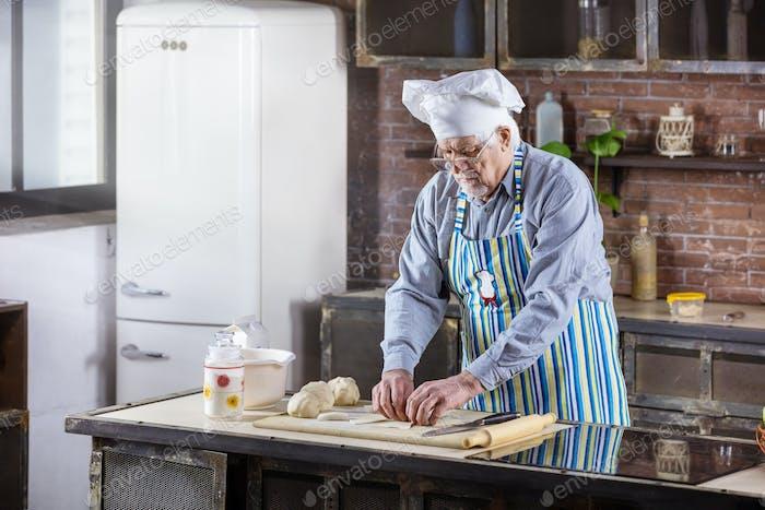 Senior man in chef hat preparing pastries in kitchen