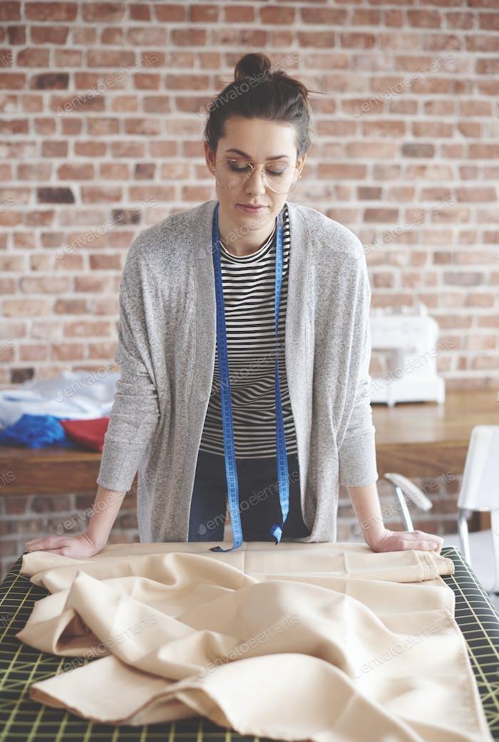 Weibliche Schneiderin arbeiten an ihrem Tisch